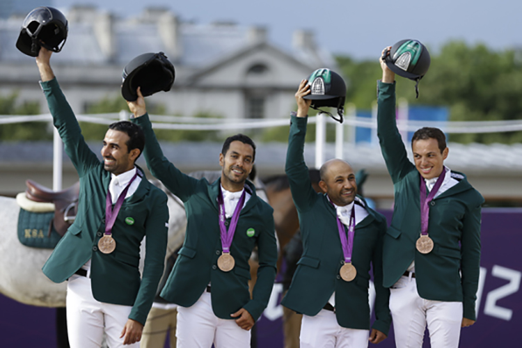 Saudi Arabia's Prince Abdullah Al Saud, Kamal Bahamdan, Ramzy Al Duhami, and Abdullah Waleed Sharbatly, from left, wave to the crowd after receiving the bronze medal in the equestrian show jumping team competition, at the 2012 Summer Olympics, Monday, Aug. 6, 2012, in London. (AP Photo/Markus Schreiber)