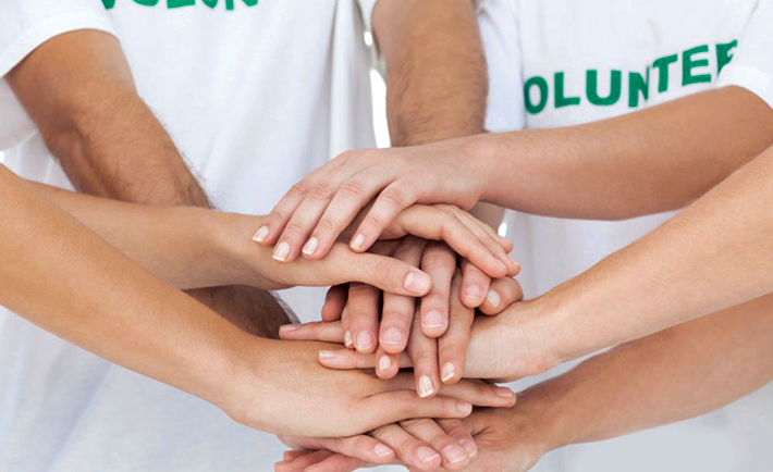group-of-volunteers-in-white-shirts-with-hands-together