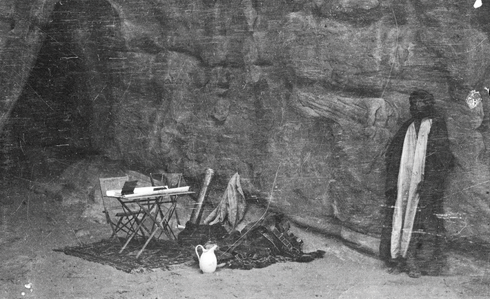 Shakespear's camping gear and Arab figure by rock face and cave, probably in mountains in vicinity of Wadi Iram/Yatun Aqabah.