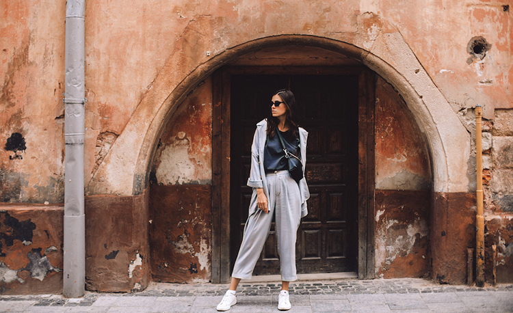 Women walking near old door. Girl dress in t-shirt, jacket and pants. Minimalist grey color look, lifestyle fashion portrait of young stylish hipster woman walking on the street, wearing trendy outfit; Shutterstock ID 1527800102; purchase_order: 23